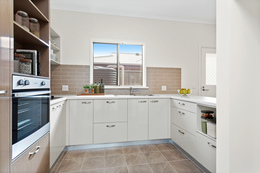 A display of a well fitted modern kitchen at Unit 29 at Oaklands Park Retirement Living